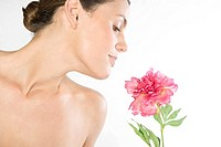 Nude woman smelling pink flower