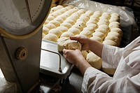 Baker Weighing Balls of Bread Dough