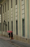 Woman walking holding an umbrella on a sidewalk in Prague