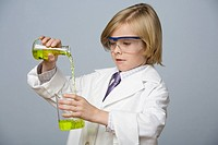 Boy pouring liquid into beaker