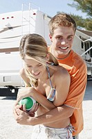 Young couple playing with football on beach