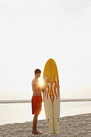 Teenage boy standing with surfboard on beach