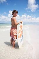 Boy holding skimboard in ocean