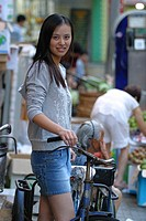 All natural Asian woman holds bicycle with street market