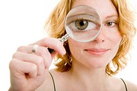 Young woman looking through a round magnifying glass