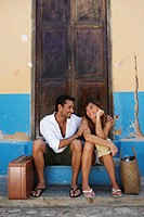 Couple sitting with suitcases (thumbnail)