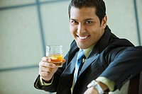 Hispanic businessman drinking mixed drink