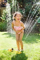 Hispanic girl playing in water sprinkler