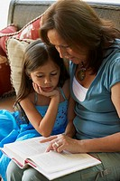 Hispanic grandmother reading to granddaughter
