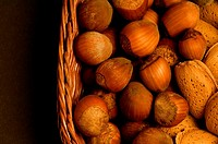 Close_up of almonds and chestnuts in a wicker basket