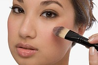 Portrait of a young woman applying make-up (thumbnail)