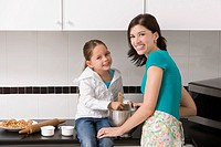 Young woman making cookies with her daughter in the kitchen