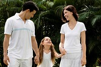 Young couple walking with their daughter in a garden and smiling
