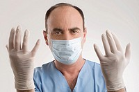 Portrait of a male surgeon wearing surgical glove and surgical mask