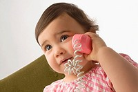 Close_up of a girl playing with a toy phone