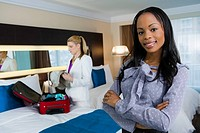 Portrait of a businesswoman smiling with another businesswoman packing her luggage