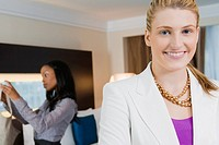 Portrait of a businesswoman smiling with another businesswoman standing in the background