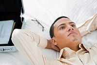 Businessman lying on the bed and thinking