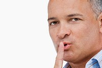 Portrait of a mature man gesturing with his finger on his lips (thumbnail)