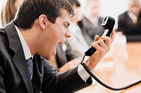 Close_up of a businessman shouting in front of a telephone receiver