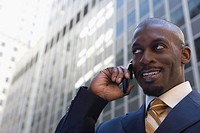 Low angle view of a businessman talking on a mobile phone and smiling