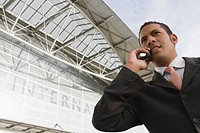 Low angle view of a businessman talking on a mobile phone outside an airport