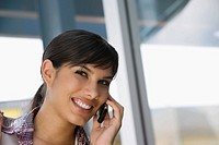 Close_up of a young woman talking on a mobile phone and smiling