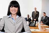 Portrait of a businesswoman smiling with her colleagues in the background (thumbnail)