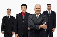 Portrait of a businessman smiling with three businessmen standing behind him