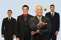 Businessman catching a rubber band ball with three businessmen standing behind him