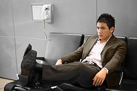 Businessman reclining on a bench at an airport