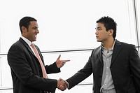 Two businessmen shaking hands at an airport