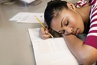 Close_up of a young man napping on a book