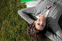 Portrait of a young woman lying in a lawn