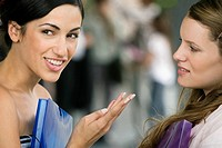 Portrait of a young woman talking to her friend and smiling