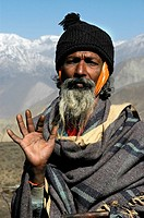 Portrait Hindu pilgrim sadhu with beard and woolen cap shows his hand in front of snow_covered mountains Muktinath Mustang Annapurna Region Nepal