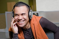 Close-up of a young man listening to music and smiling (thumbnail)