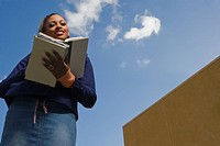 Low angle view of a young woman reading a textbook