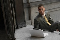 Portrait of a businessman sitting on steps and using a laptop