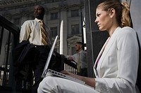 Side profile of a businesswoman using a laptop with two businessmen in the background