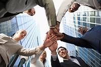 Low angle view of business executives stacking hands