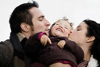 Close-up of a couple kissing their daughter (thumbnail)