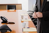 Mid section view of a businessman standing in a conference room