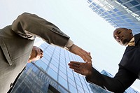 Low angle view of two businessmen shaking hands