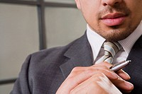 Close_up of a businessman holding a pen