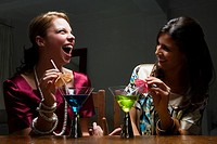 Two young women drinking cocktail and smiling
