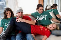 Three young people sitting on a couch with a young woman lying on them
