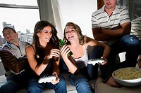 Two young women toasting with beer bottles and two young men sitting beside them