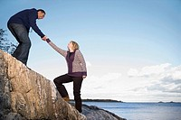 Mature man helping a mature woman to climb a rock