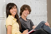 Portrait of a teenage boy and a teenage girl sitting together and smiling